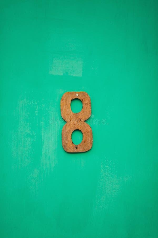 Cuadro de madera ocho número en la pared esmeralda foto de archivo
