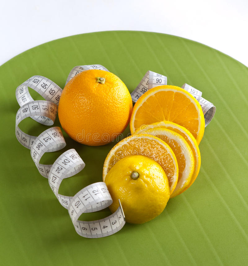 Cuadro de naranjas y de la cinta métrica imagen de archivo