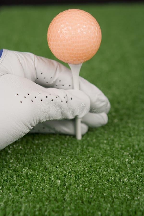 Cuadro de una bola que junta con te de la mano con guantes del golf para arriba imagen de archivo