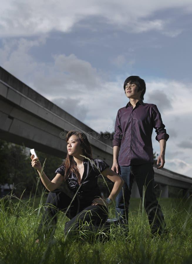 Cuadro trenzado de los pares asiáticos que presentan al aire libre foto de archivo