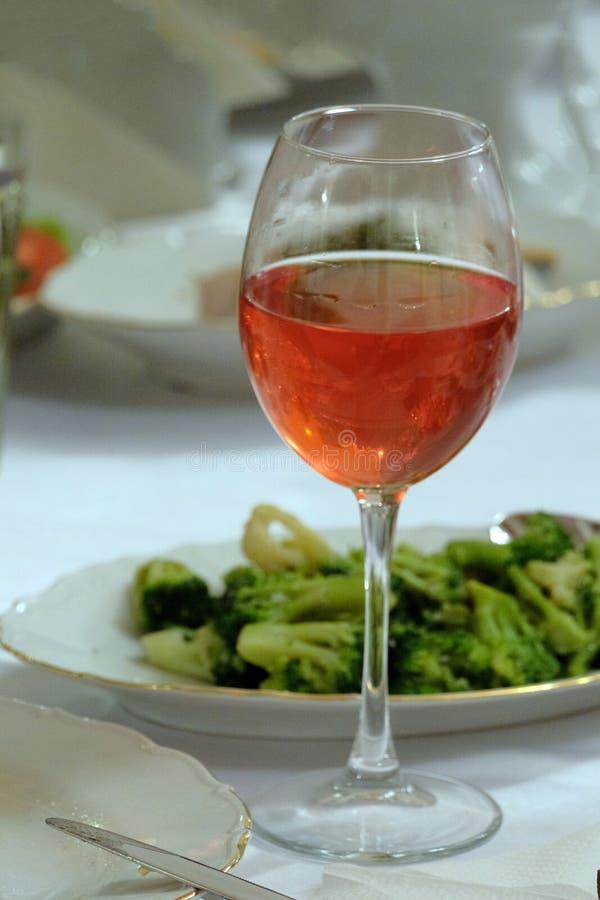 Cuadro vertical Un vidrio de vino rosado en una tabla al lado de una ensalada del bróculi imagen de archivo libre de regalías