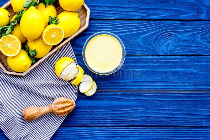 Cuajada de limón Crema dulce para los postres cerca de los limones en bandeja en espacio de madera azul de la copia de la opinión imagen de archivo libre de regalías