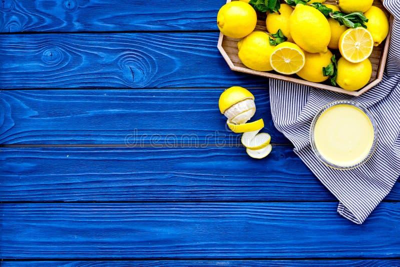Cuajada de limón Crema dulce para los postres cerca de los limones en bandeja en espacio de madera azul de la copia de la opinión fotos de archivo