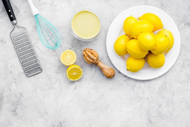 Cuajada de limón del cocinero Crema dulce en el cuenco, frutas, utensilios de la cocina en espacio gris de la copia de la opinión foto de archivo