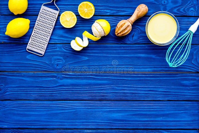 Cuajada de limón del cocinero La crema dulce en el cuenco, frutas, utensilios rallador de la cocina y bate en copia de madera azu imágenes de archivo libres de regalías