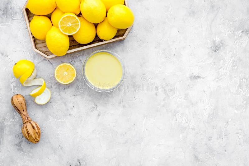 Cuajada de limón La crema dulce para los postres cerca de los limones y el juicer en la opinión superior del fondo gris copian el fotografía de archivo