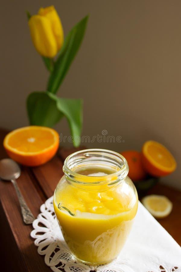 cuajada del Anaranjado-limón y rebanadas de naranjas y de limones en una superficie de madera Estilo rústico foto de archivo libre de regalías