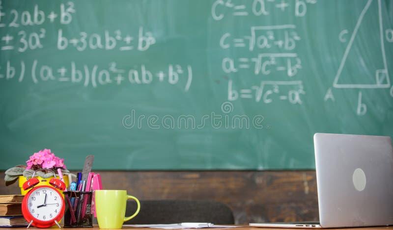 Cualidades de los profesores Condiciones de trabajo que los profesores anticipados deben considerar Tabla con el despertador de l imagenes de archivo