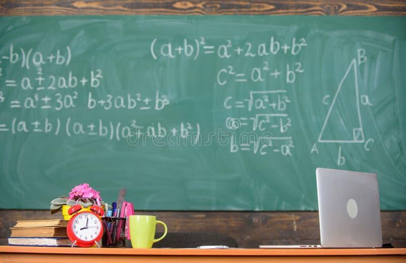 Cualidades de los profesores Tabla con los libros del despertador de las fuentes de escuela y el fondo de la pizarra de la sala d foto de archivo