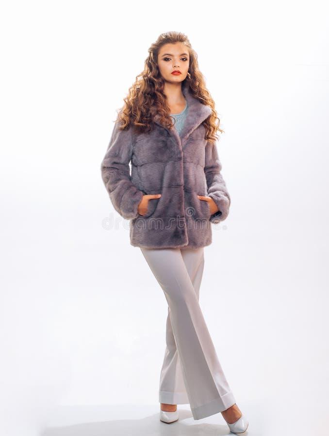 Cuando el tiempo se refresca sobre su ropa de sport Mujer bonita en abrigo de pieles de moda El modelo de moda lleva la piel real fotos de archivo libres de regalías