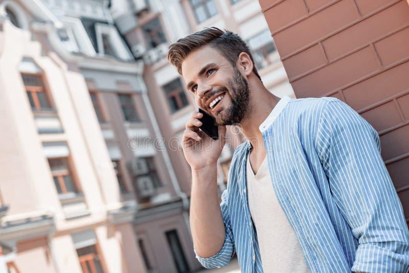 Cuando la cuenta de fideicomiso es alta, la comunicación es fácil, inmediata, y eficaz Hombre moreno sonriente con los ojos azule imagenes de archivo