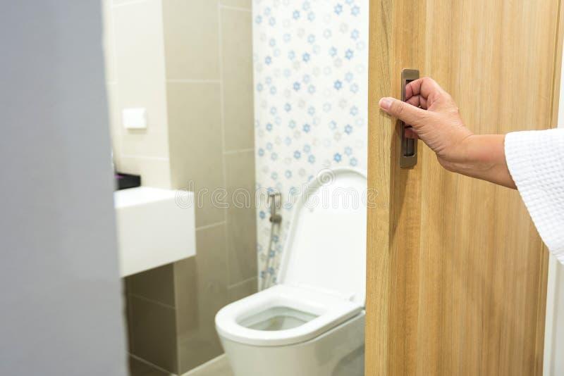 Cuarto de baño abierto de la puerta del retrete de la mano foto de archivo libre de regalías