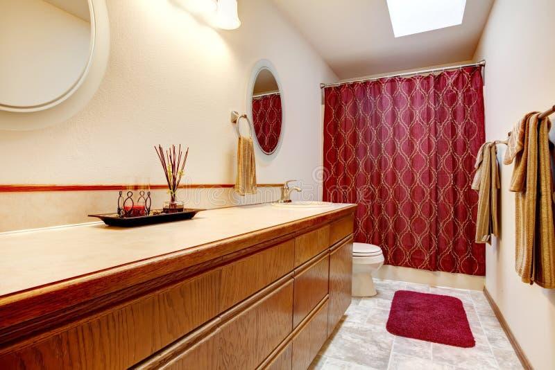 Cuarto de baño acogedor con la manta y las cortinas rojas imágenes de archivo libres de regalías