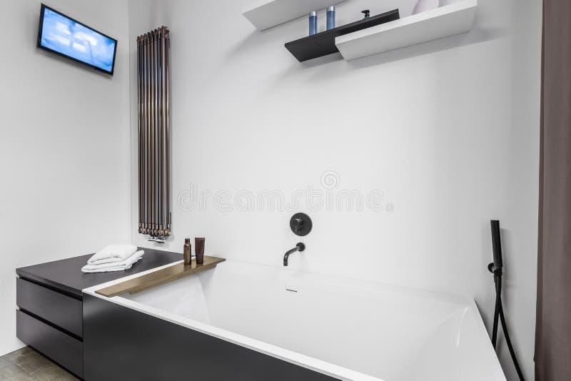 Cuarto de baño con la TV y la bañera foto de archivo libre de regalías