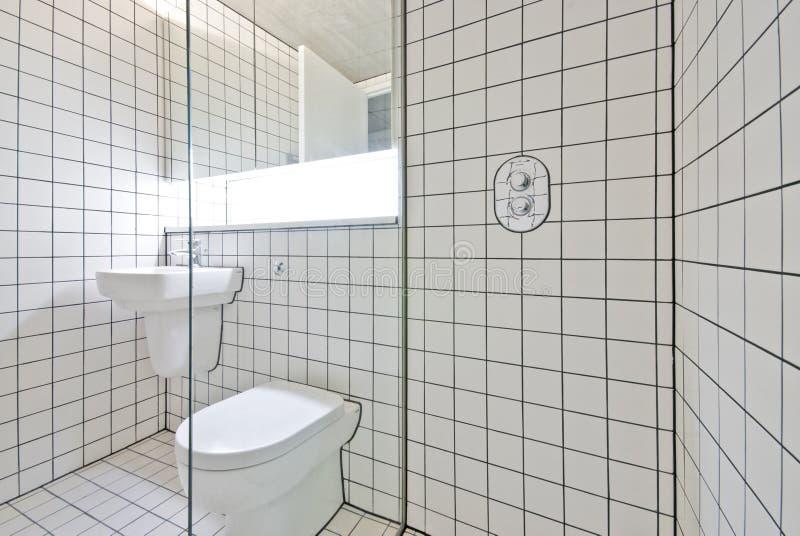 Cuarto de baño contemporáneo con las paredes embaldosadas blancas retras imagen de archivo
