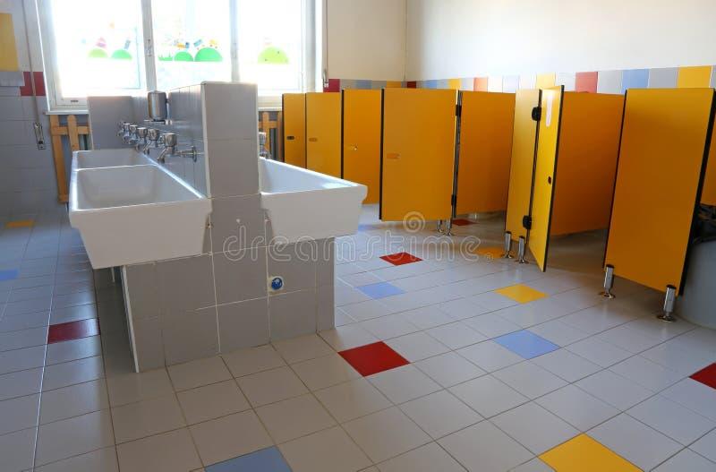 Cuarto de baño de la guardería con los fregaderos de cerámica blancos imágenes de archivo libres de regalías