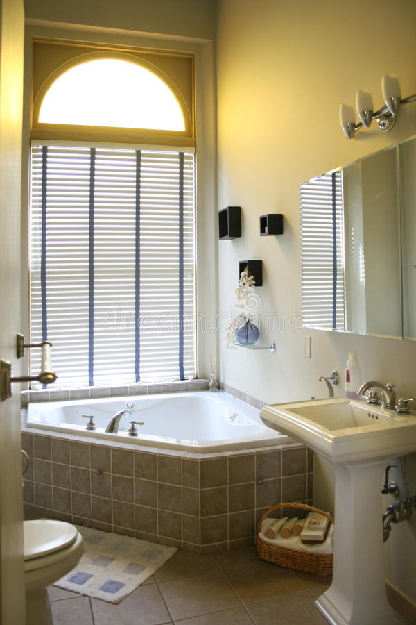 Cuarto de baño exclusivo con la tina de la esquina. imagen de archivo