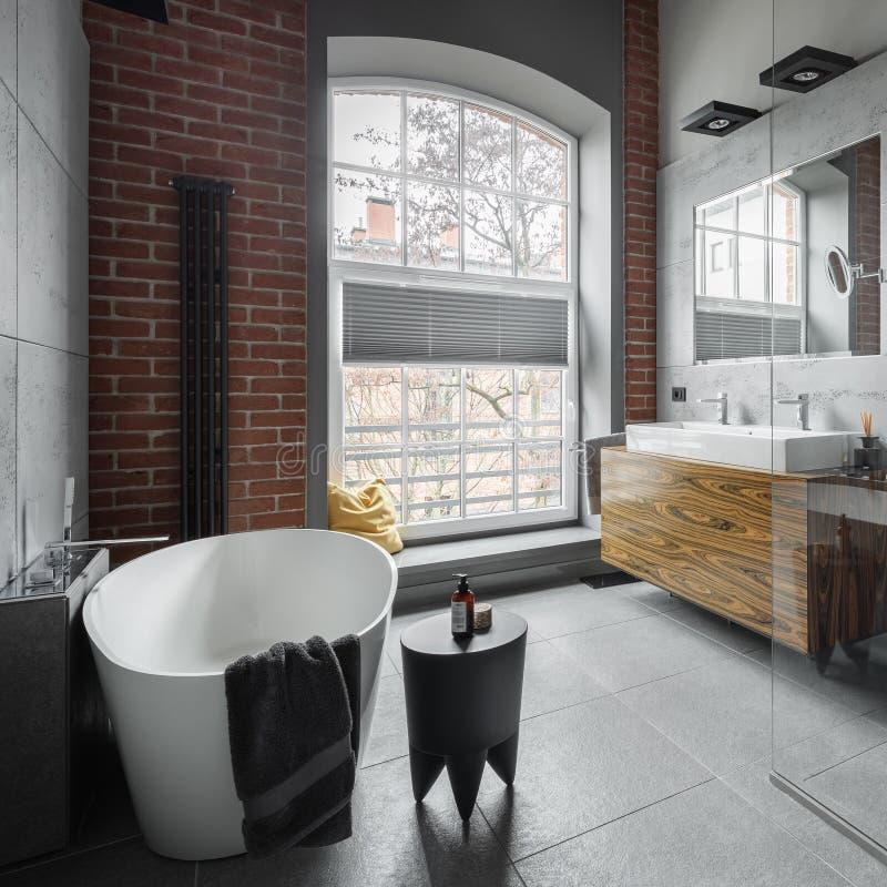 Cuarto de baño industrial del estilo con la bañera oval fotos de archivo libres de regalías