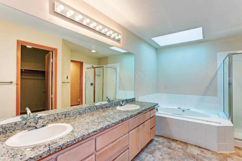 Cuarto de baño ligero y airoso con la tina echada en chorro imagen de archivo