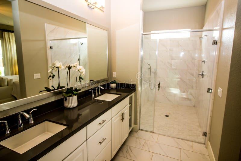 Cuarto de baño moderno con su y el suyo fregadero contrario del mármol fotos de archivo