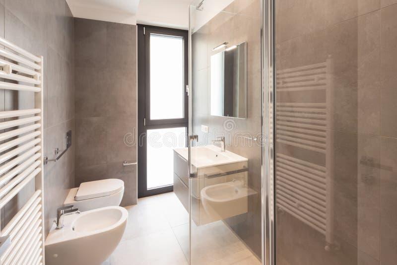 Cuarto de baño moderno minimalista con las tejas grandes fotografía de archivo libre de regalías