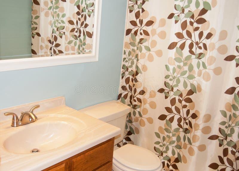 Cuarto de baño nuevamente renovado con las paredes y la cortina de ducha azules foto de archivo