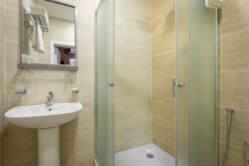 Cuarto de baño, tejas y colores brillantes de la escoba, ducha con las puertas heladas, espejo sobre el fregadero Colgante de una imágenes de archivo libres de regalías