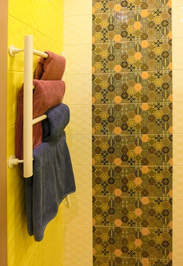 Cuarto de baño vacío con la pared coloreada gris de la ducha detrás del estante que se calienta del metal blanco foto de archivo libre de regalías