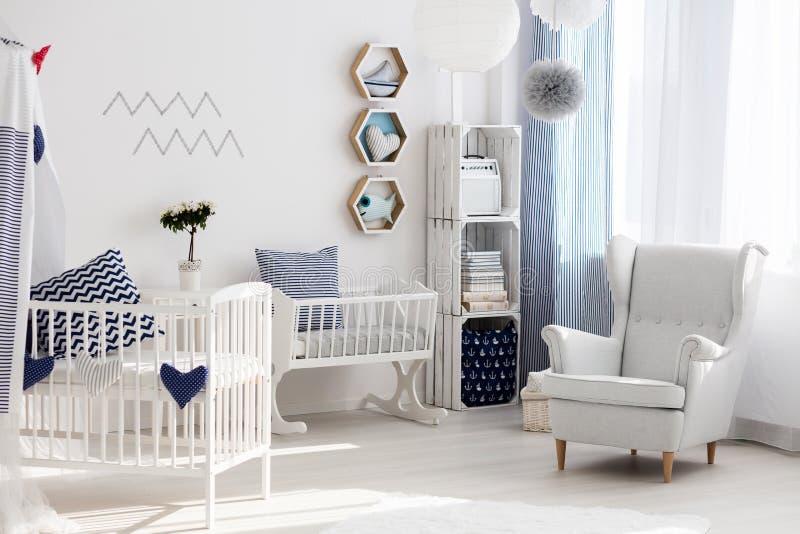 Cuarto de niños con la silla y la cuna blancas fotos de archivo libres de regalías