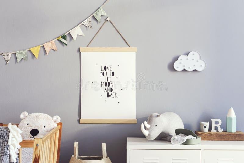 Cuarto de ni?os escandinavo elegante interior con mofa colgante encima del cartel, de los juguetes naturales, de los osos de pelu foto de archivo