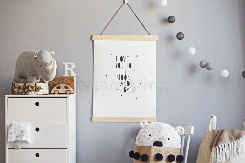 Cuarto de ni?os escandinavo elegante interior con mofa colgante encima del cartel, de los juguetes naturales, de los osos de pelu fotos de archivo