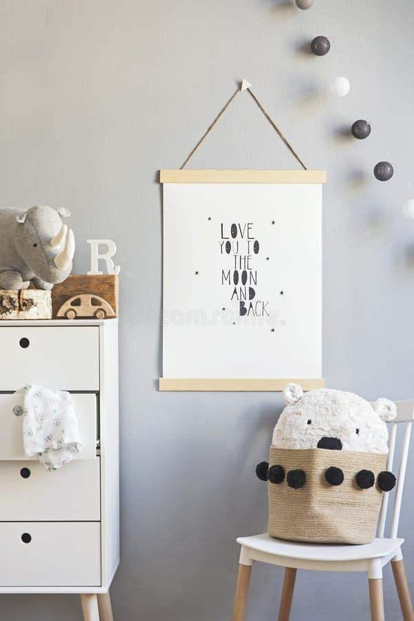 Cuarto de ni?os escandinavo elegante interior con mofa colgante encima del cartel, de los juguetes naturales, de los osos de pelu imagen de archivo