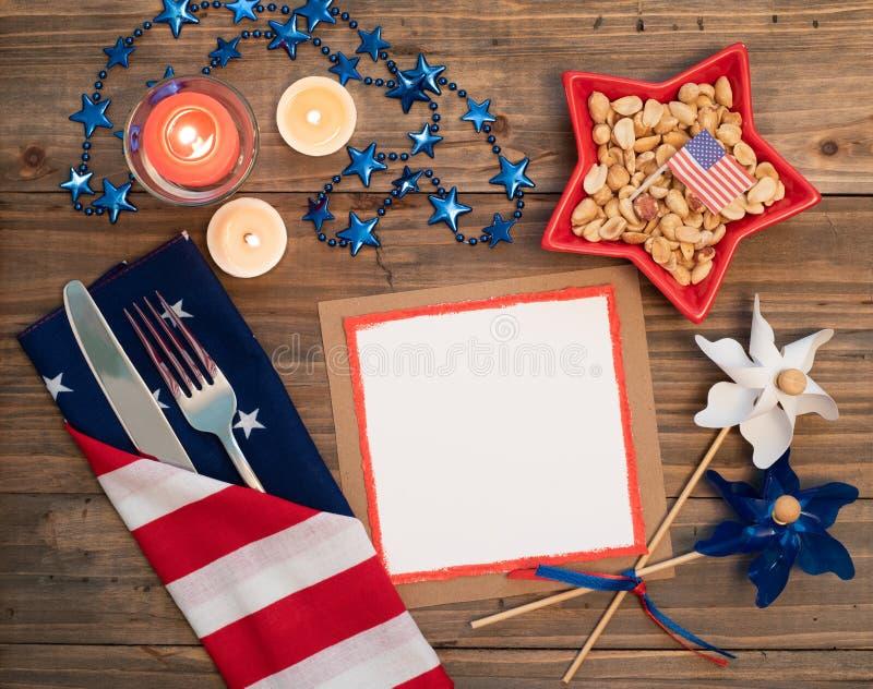 Cuarto del cubierto de la tabla de julio con las decoraciones rojas, blancas y azules y tarjeta en blanco con el espacio de la co imagen de archivo