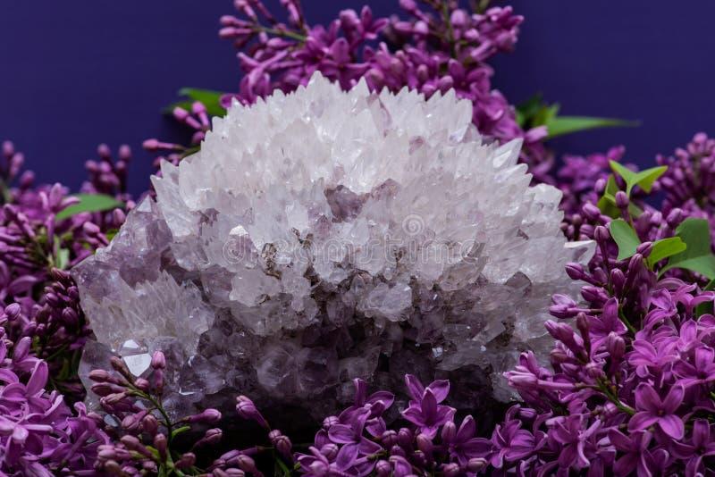 Cuarzo de la aguja con el esp?cimen de la amatista rodeado por la flor p?rpura de la lila fotos de archivo libres de regalías