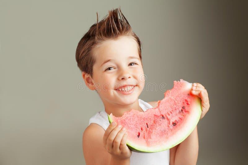 Cuatro años felices del muchacho que sonríe con la sandía fotos de archivo