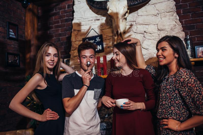 Cuatro adolescentes frescos que llevan la ropa casual que presenta para la cámara en un elegante con diseño interior de la casa d imagen de archivo libre de regalías
