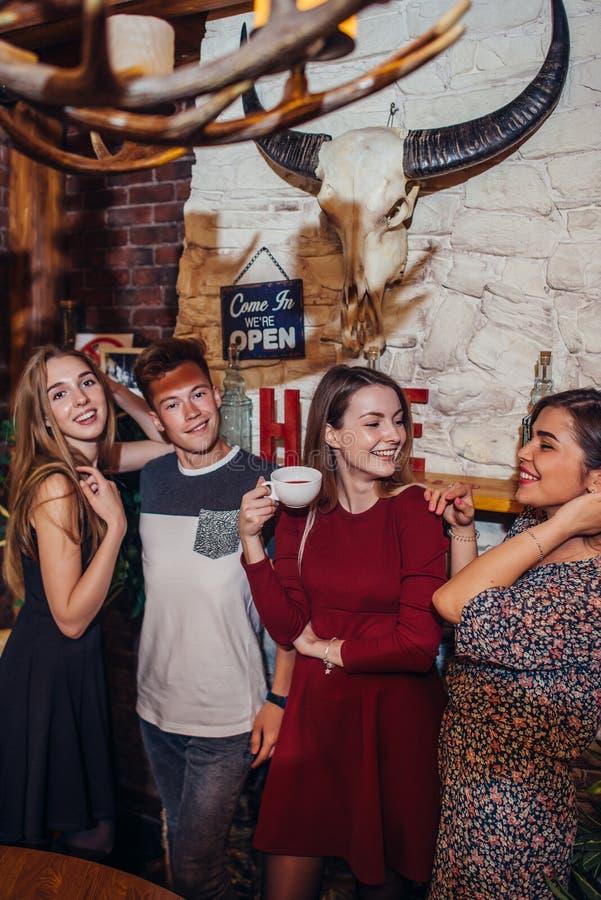 Cuatro adolescentes frescos que llevan la ropa casual que presenta para la cámara en un elegante con diseño interior de la casa d imagen de archivo
