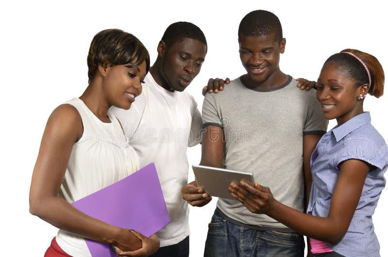 Cuatro amigos africanos que miran la tableta fotografía de archivo libre de regalías