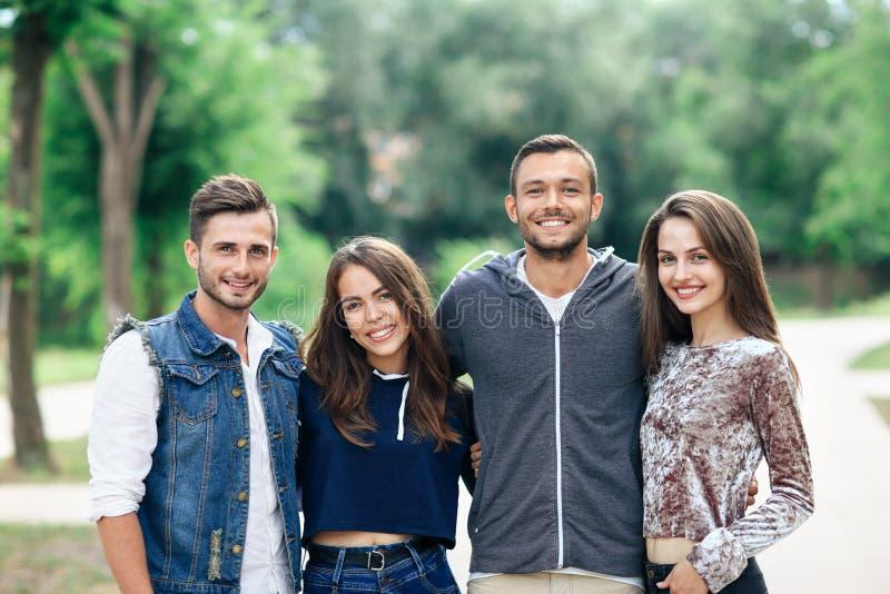 Cuatro amigos alegres jovenes que caminan en día caliente imagen de archivo