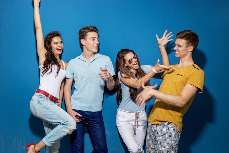 Cuatro amigos apuestos están riendo mientras que se colocan delante de la pared azul que tiene miradas confiadas y felices fotografía de archivo