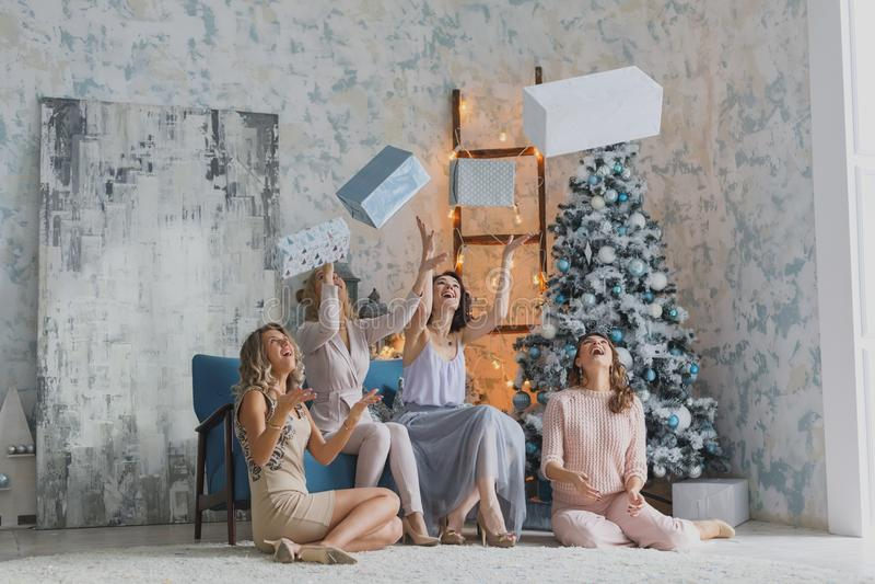 Cuatro amigos bonitos alegres que celebran la fiesta del Año Nuevo o de cumpleaños, se divierten, alcohol de la bebida, bailando  imagen de archivo libre de regalías