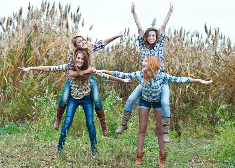 Cuatro amigos de muchachas adolescentes felices que se divierten al aire libre fotos de archivo libres de regalías