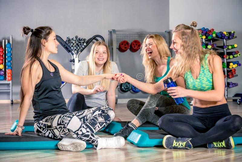 Cuatro amigos después de un entrenamiento en hablar del gimnasio imagenes de archivo