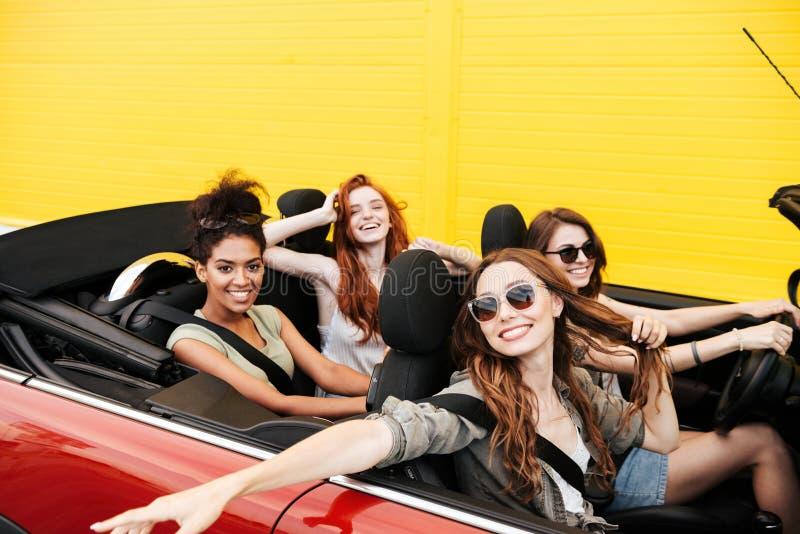 Cuatro amigos emocionales felices de las mujeres jovenes que se sientan en coche fotos de archivo