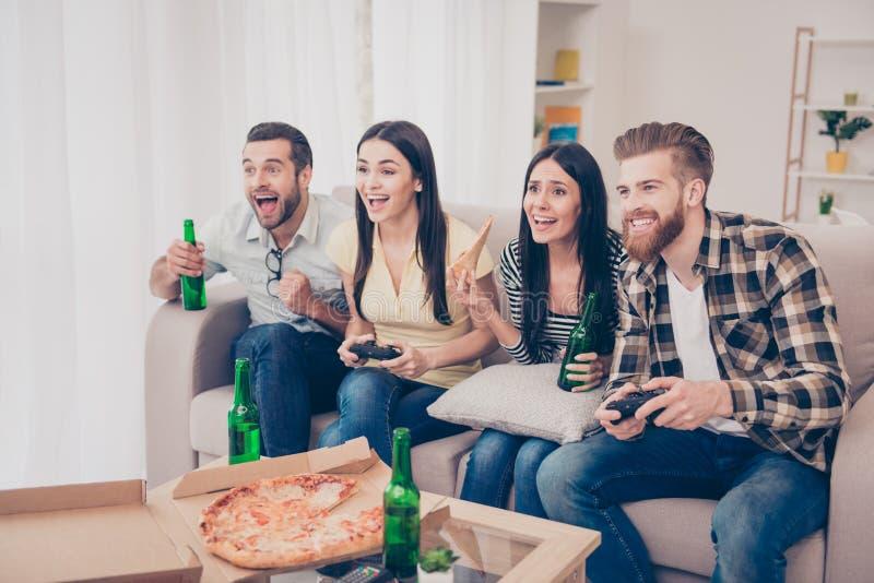 Cuatro amigos, fans de juegos, sentándose en el sofá en acogedor agradable ho fotos de archivo