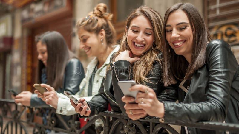 Cuatro amigos felices que miran medios sociales de Internet en teléfono celular imagen de archivo