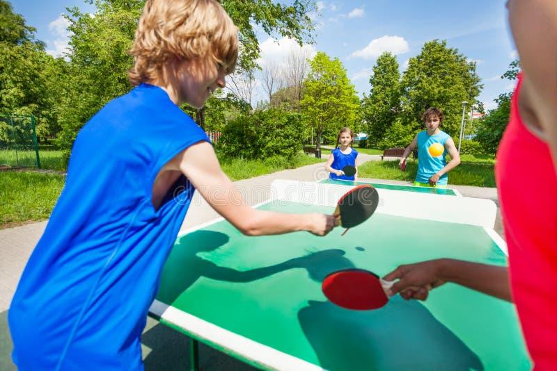 Cuatro amigos internacionales que juegan a ping-pong foto de archivo