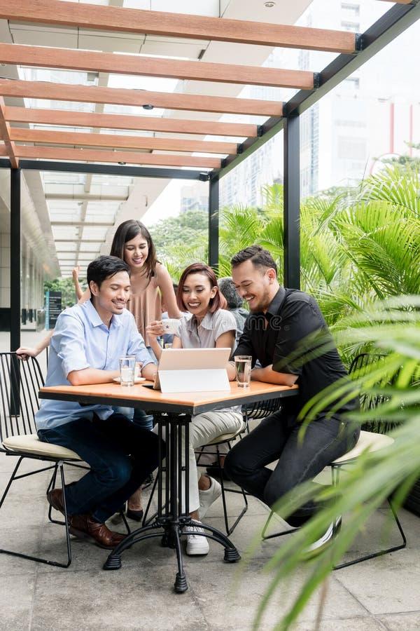 Cuatro amigos jovenes asiáticos que miran junto el contenido en línea divertido foto de archivo