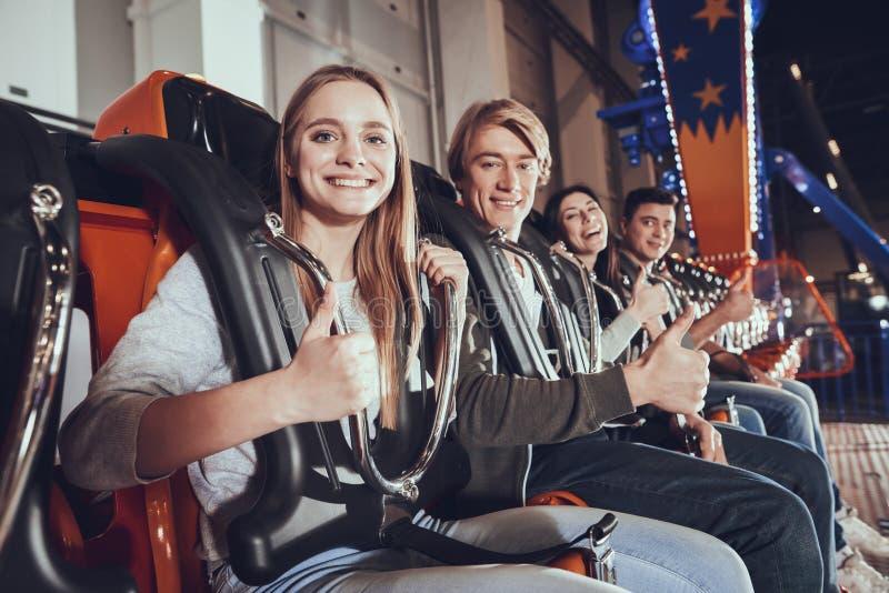 Cuatro amigos jovenes aumentan su finger para arriba imagen de archivo libre de regalías