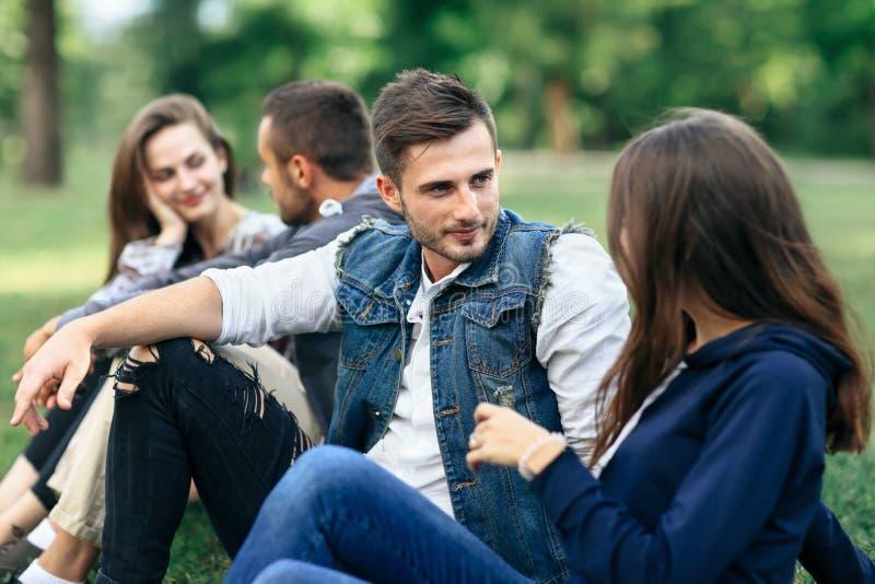 Cuatro amigos jovenes que miran uno a y comunican al aire libre foto de archivo